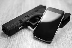 Une arme à feu et un téléphone intelligent moderne, noirs et blancs Photo stock