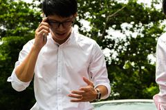 Une assurance auto d'appel d'homme pour le halp avec les parties de la voiture photographie stock libre de droits