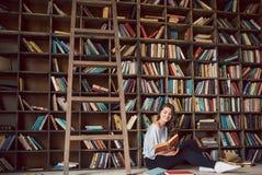 Une atmosphère de la lecture passionnée d'histoire jeune femme de livres de lecture belle Pièce confortable de bibliothèque Photos stock