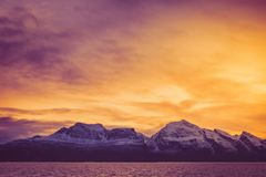 Une aube ardente au-dessus des crêtes neigeuses du fjord photo libre de droits