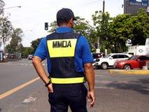 Une autorité du trafic se tient à une intersection de route Photo stock