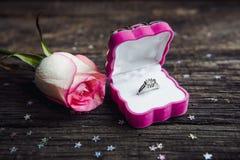 Une bague de fiançailles de diamant dans une boîte de bijoux, tir à côté d'une rose rouge Images stock