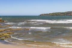 Une baie pittoresque d'océan avec une plage sablonneuse et une ville sur la montagne à l'arrière-plan photos libres de droits