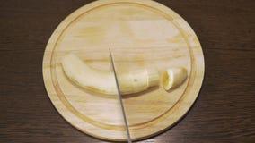 Une banane épluchée, il est coupé avec un couteau en plusieurs morceaux clips vidéos