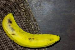 Une banane déchirée sur le plan rapproché en bois photo stock