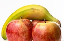 Une banane et trois pommes Image libre de droits
