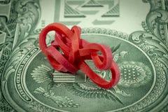 Une bande élastique tordue sur le billet de banque du dollar photographie stock libre de droits