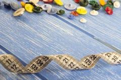 Une bande de centimètre et des boutons colorés sur les boutons en bois bleus d'un fond photo libre de droits