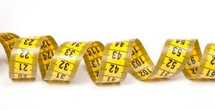 Une bande de mesure jaune enroulée Images stock