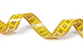 Une bande de mesure jaune enroulée Image stock