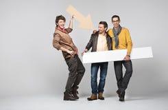 Une bande des amis mâles avec des signes Photographie stock libre de droits