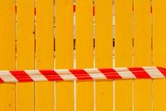 Une bande rouge et blanche de signal contre une barrière jaune image libre de droits