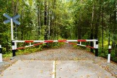 Une barrière à travers le chemin forestier solitaire Photographie stock libre de droits