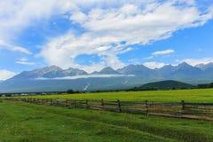 Une barrière en bois et une clairière verte contre le contexte des montagnes Image stock