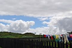 Une barrière en bois et une pelouse verte avec la blanchisserie traînant pour sécher dans le vent Photo libre de droits