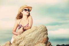 Une belle blonde avec le chapeau et les lunettes de soleil regardant fixement dans le dist Image libre de droits