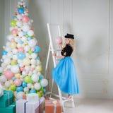 Une belle blonde dans un costume de carnaval décore l'arbre des ballons Jeune femme avec du charme dans une jupe bleue sinueuse photos stock