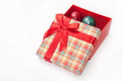 Une belle boîte rouge avec un arc rouge et des oeufs de pâques Photo libre de droits