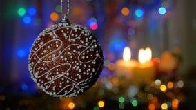 Une belle boule rouge Décorations d'an neuf et de Noël Bougies brûlantes Guirlandes de clignotant Fond brouillé banque de vidéos