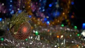 Une belle boule rouge Décorations d'an neuf et de Noël Guirlandes de clignotant Fond brouillé banque de vidéos