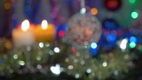 Une belle boule rouge Décorations d'an neuf et de Noël Guirlandes de clignotant Fond brouillé Mouvement de l'appareil-photo banque de vidéos