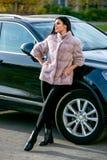 Une belle brune dans un manteau de fourrure léger et des pantalons noirs se tient près de la voiture un jour ensoleillé et un sou photographie stock libre de droits