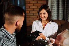 Une belle brune donne un cadeau à son ami dans un restaurant une date Image libre de droits