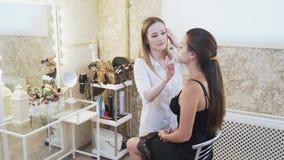 Une belle brune va à un événement, elle est venue à un artiste de maquillage pour composer et à une coiffure La fille s'assied banque de vidéos