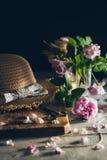 Une belle composition romantique en mode de vie avec le chapeau de paille et les pétales de roses sur le fond en bois et rustique Photo libre de droits