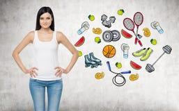 Une belle dame de brune qui essaye de faire un choix en faveur d'une certaine activité de sport Des icônes colorées de sport sont photos libres de droits