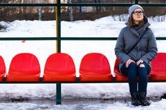 Une belle et jeune fille avec des verres s'assied sur un banc des chaises rouges images stock