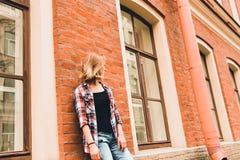 Une belle et jeune fille se tient près d'une maison de brique avec de grandes fenêtres en bois images libres de droits