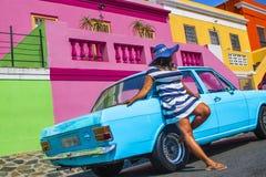 Une belle femme africaine dans une robe ray?e bleue et blanche devant un cru Ford Cortina et les maisons traditionnelles de la BO images stock