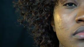 Une belle femme afro-américaine tranquillement tient et clignote un oeil, fin vers le haut du tir clips vidéos