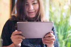 Une belle femme asiatique avec la participation souriante de visage, à l'aide et regardant du PC de comprimé en café moderne images libres de droits