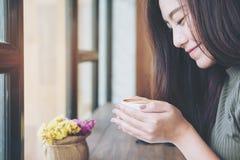 Une belle femme asiatique tenant et sentant la tasse de café chaude en café de grenier avec se sentir heureux photographie stock