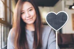 Une belle femme asiatique tenant un signe vide de tableau noir de forme de coeur avec se sentir heureux Image stock