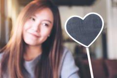 Une belle femme asiatique tenant un signe vide de tableau noir de forme de coeur avec se sentir heureux Image libre de droits