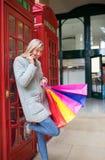 Une belle femme avec des paniers dans la rue d'achats, Londres Photographie stock