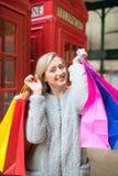 Une belle femme avec des paniers dans la rue d'achats, Londres Images stock