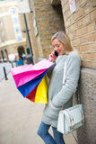 Une belle femme avec des paniers dans la rue d'achats, Londres Images libres de droits