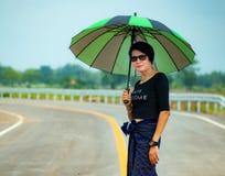 Une belle femme avec le parapluie vert se tenant sur la route moyenne dans la campagne photo stock