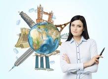 Une belle femme avec le stylo de marque et un globe avec les endroits touristiques célèbres esquissés dans le monde Éléments de c Photographie stock libre de droits