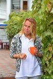 Une belle femme avec une tasse orange et une prune de la vigne Photographie stock