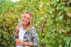 Une belle femme avec une tasse orange et une prune de la vigne Photos libres de droits