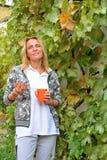 Une belle femme avec une tasse orange et une prune de la vigne Photo libre de droits