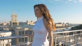 Une belle femme dans des vêtements blancs marche le long de la rue banque de vidéos