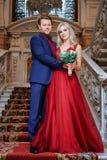 Une belle femme dans une robe rouge se tient avec un homme, jeunes mariés, nouveaux mariés heureux photographie stock libre de droits