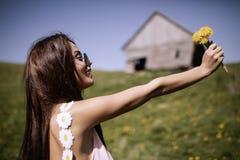 Une belle femme dans sa robe apprécie une clairière de fleur de montagne Images stock