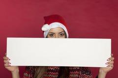 Une belle femme dans un chapeau de Noël se cache derrière une tache pour le C.A. Photographie stock